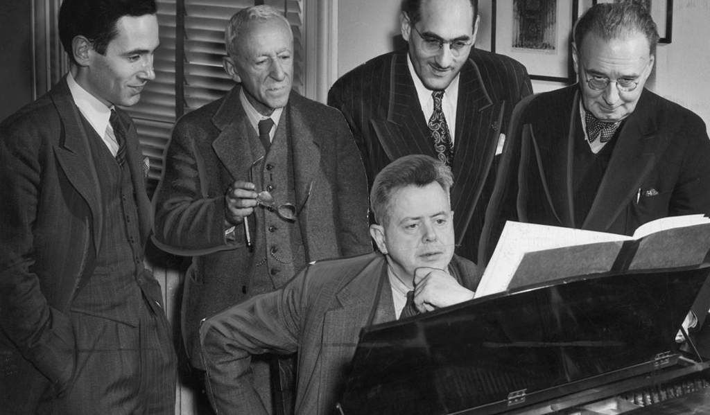 Sir Ernest MacMillan at the piano with Godfrey Ridout, Prof. Leo Smith, John Weinzweig and Dr. Healey Willan surrounding him. The photograph was taken circa. 1948 by Nott and Mell.