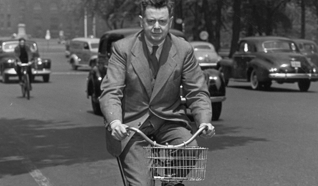 Sir Ernest MacMillan riding a bicycle along University Avenue in June, 1942 as he was leaving the Toronto Conservatory of Music for lunch.